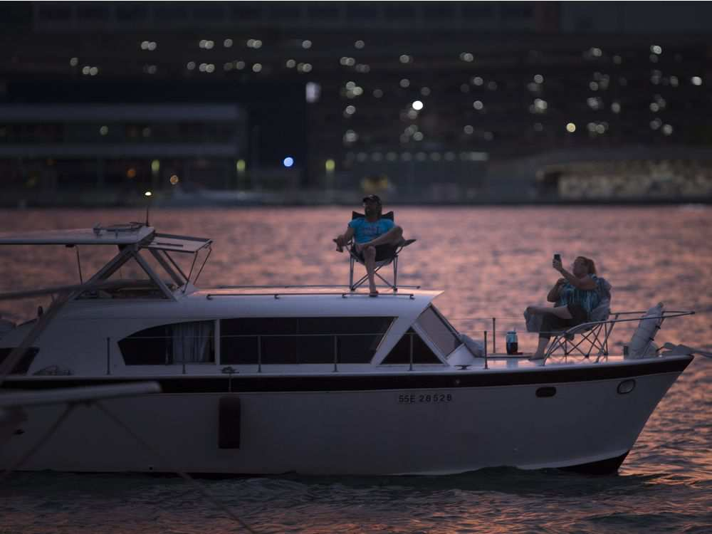 A pair of boaters take in the third night of the LiUNA Bluesfest Windsor from the comfort of their boat, Saturday, July 14, 2018. DAX MELMER / WINDSOR STAR